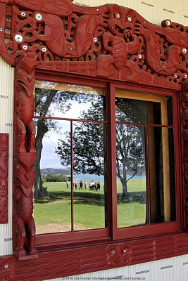 Window of Te Whare Runanga Meeting House reflecting front lawn