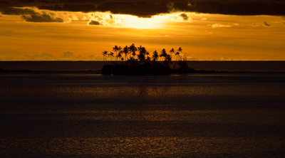 Sunset south of Bora Bora with palm trees on a motu